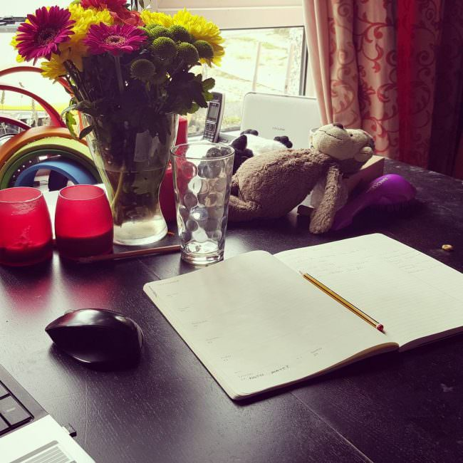"My ""desk"" yesterday. Note the remnants of the kid's breakfast to the right of my diary."